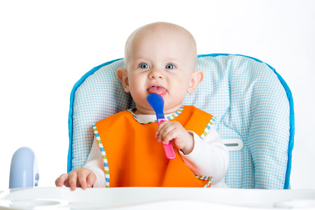 smiling baby with spoon waiting food photo