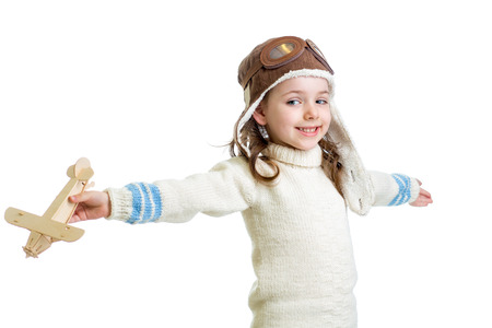 kid dressed as pilot and playing with wooden airplane toy isolated on white background photo