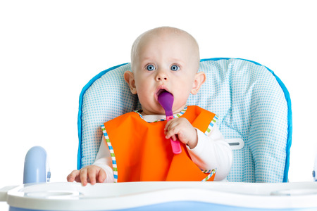 highchair: baby with spoon in highchair
