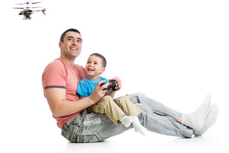 Child boy and dad playing with RC helicopter toy photo