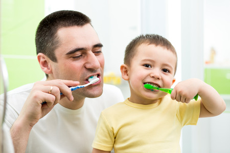 tooth cleaning: father and kid son brushing teeth in bathroom
