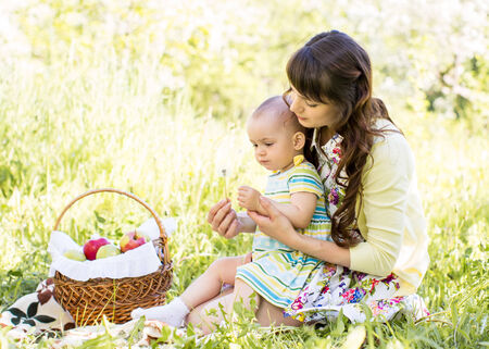 baby and mom sit with basket outdoors photo