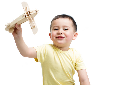 smiling kid boy playing with wooden airplane toy photo