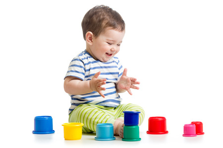 funny baby playing with colourful cup toys on floor, isolated over white photo