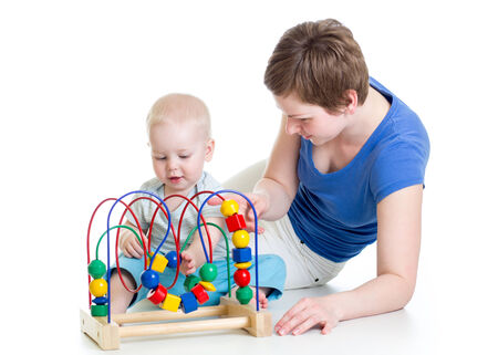 child boy and mother play with color educational toy photo