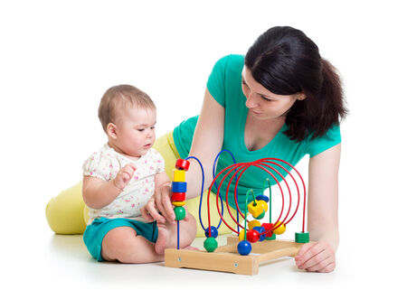 baby girl and mother play with educational toy photo