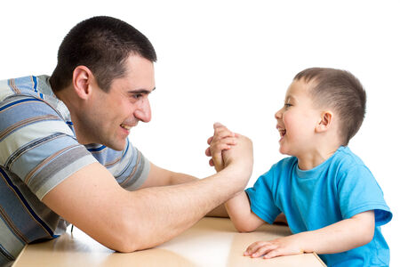 health care fight: kid boy and his dad competing in physical strength Stock Photo