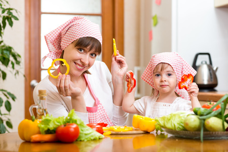 kid girl and her mother cooking in kitchen at home photo