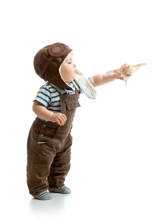 Kid boy playing with wooden plane photo