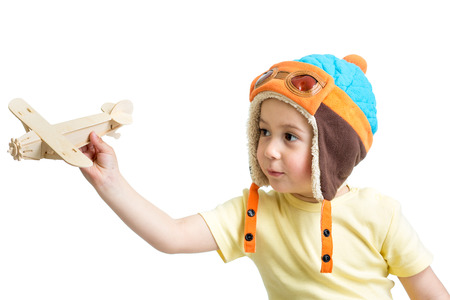 happy kid boy dressed pilot and playing with wooden airplane toy photo