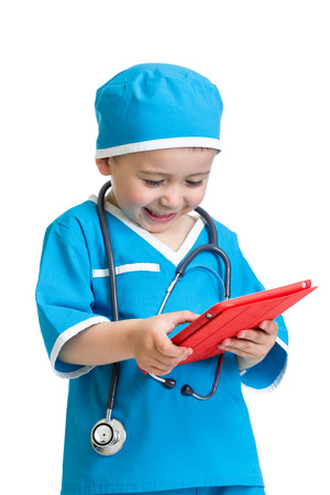 kid boy uniformed as doctor with tablet pc in hands photo