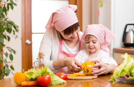 mother and kid girl preparing food to lunch photo