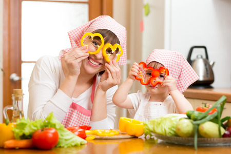cook house: mother and kid preparing healthy food and having fun Stock Photo
