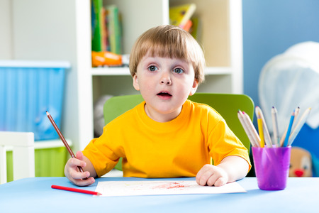 child boy drawing with pencils at table photo