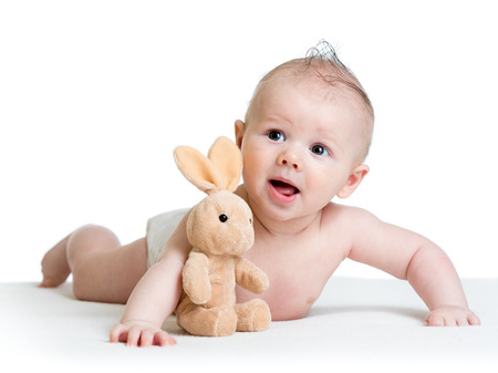 baby boy lying on tummy with bunny toy photo