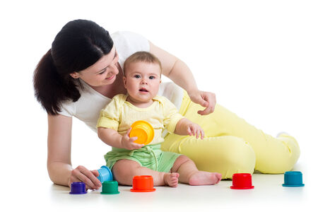 Baby girl and mother play together with cup toys photo