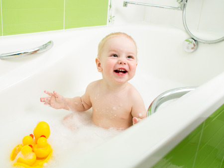 baby bath: smiling toddler boy taking bath and playing with toys Stock Photo