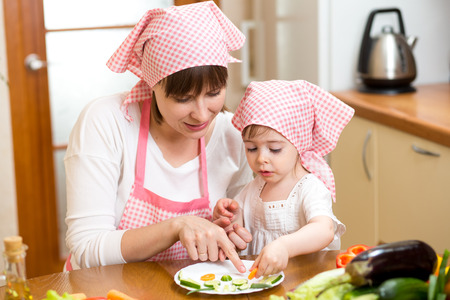 Young mother and her kid making funny vegetables dish photo