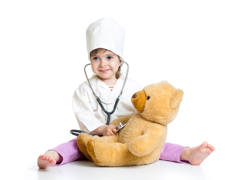 kid girl with clothes of doctor playing with toy photo