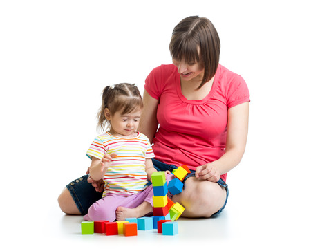 child girl and her mom play with building blocks photo