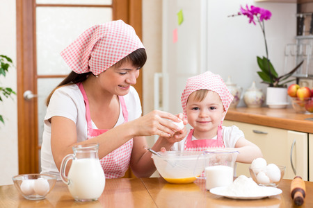Young woman and her daughter cooking together at home Stock Photo - 29119593