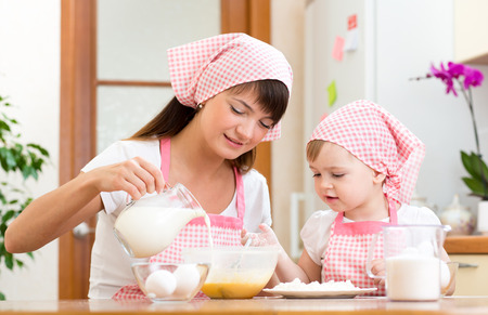 mother milk: Mother and child preparing cookies together at kitchen Stock Photo