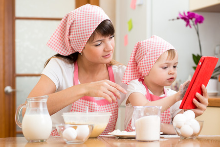 Mother and child preparing pastry together at kitchen and looking at cookbook photo
