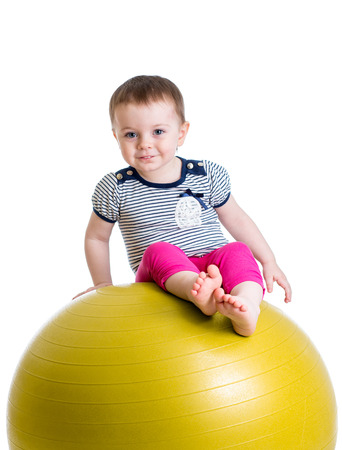 fit ball: Kid having fun with  gymnastic ball isolated