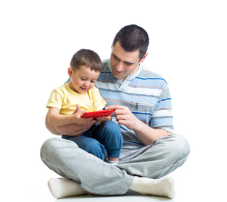 father and kid are looking to play and read tablet computer photo