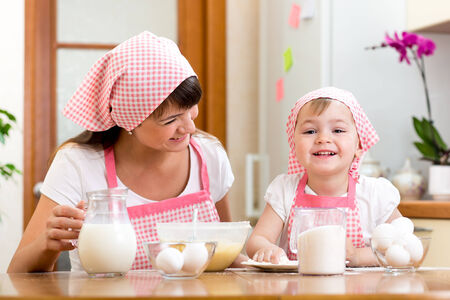 Mother and kid preparing cookies together at kitchen Stock Photo - 29200968