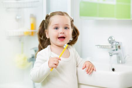 higiene: muchacha ni�o cepillarse los dientes en el ba�o