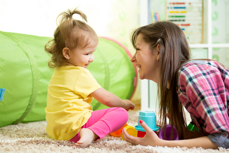 toddler playing: child girl and her mother playing together with toys