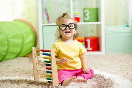 child weared glasses playing with abacus photo