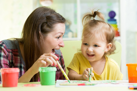 cute mother teach her daughter kid to paint photo