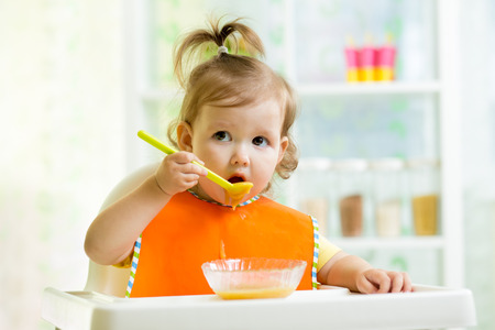 baby eating: child eating healthy food on kitchen