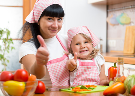 Kid girl and mother cooking and showing thumb up photo