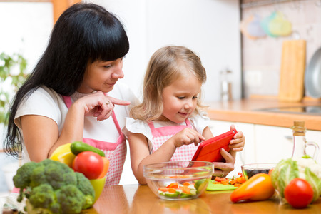 Mother and child preparing vegetables together at kitchen and looking at tablet for receipe photo