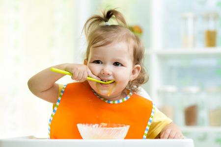 little girl eating: smiling kid eating food on kitchen