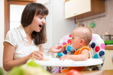 Mother feeding baby with spoon photo