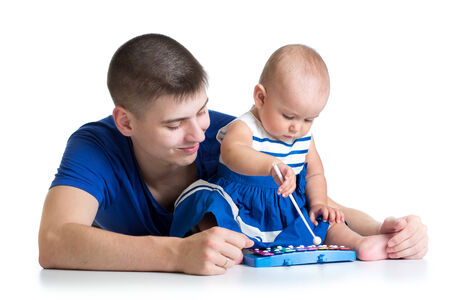 Young dad and baby girl having fun with musical toys photo