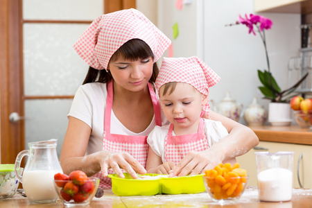Young woman and her daughter making berry fruit cake photo