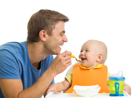 smiling baby eating food Stock Photo
