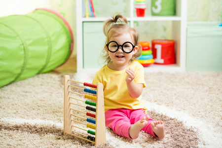 kid weared eyeglasses playing with abacus photo