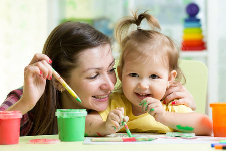 baby drawing: cute mother teach her daughter kid to paint Stock Photo