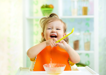 food on white: funny baby eating healthy food on kitchen Stock Photo