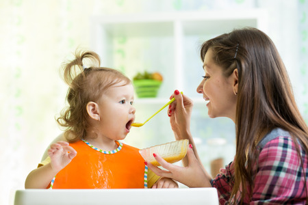 Mother feeding kid with spoon indoors photo
