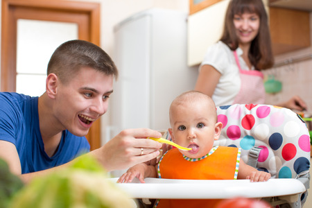 father feeding his kid and mother cooking at kitchen photo