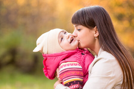 Young mother kissing kid girl outdoors in autumn park photo