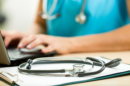 close up of female doctor working with laptop