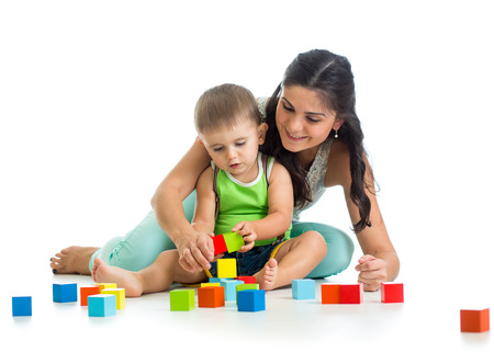 kid boy and his mother play together with construction set toy photo